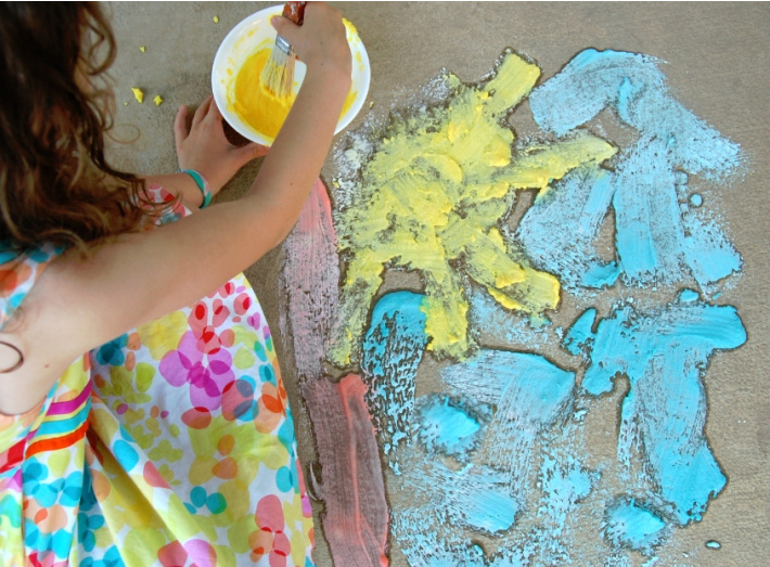 homemade fizzy sidewalk paint recipe for kids from Kids Activities Blog - girl painting a picture with fizzy sidewalk paint