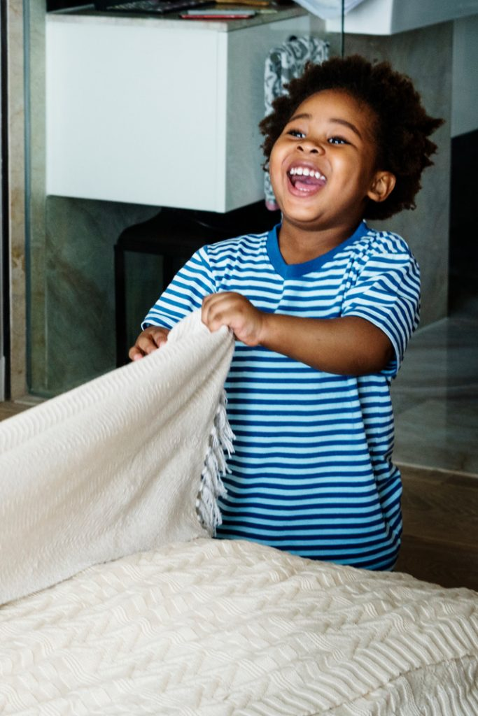 How much allowance should I pay my kids for chores?  Boy making bed at home laughing - Kids Activities Blog