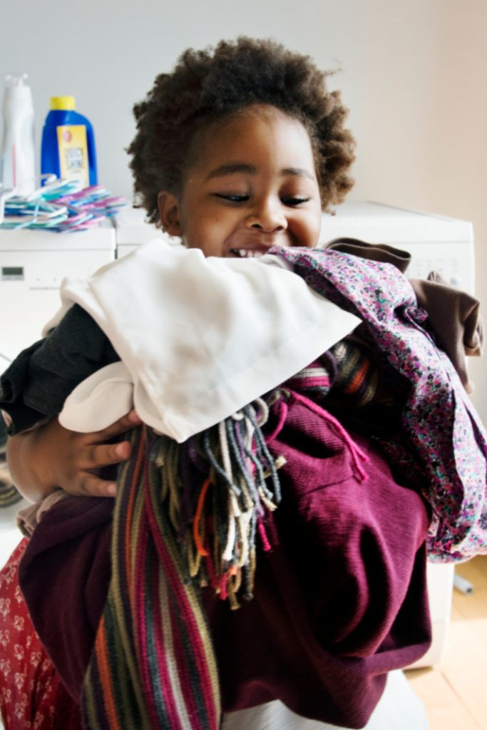 how to get kids to do chores everyday - Kids Activities Blog - child carrying clean laundry out of laundry room