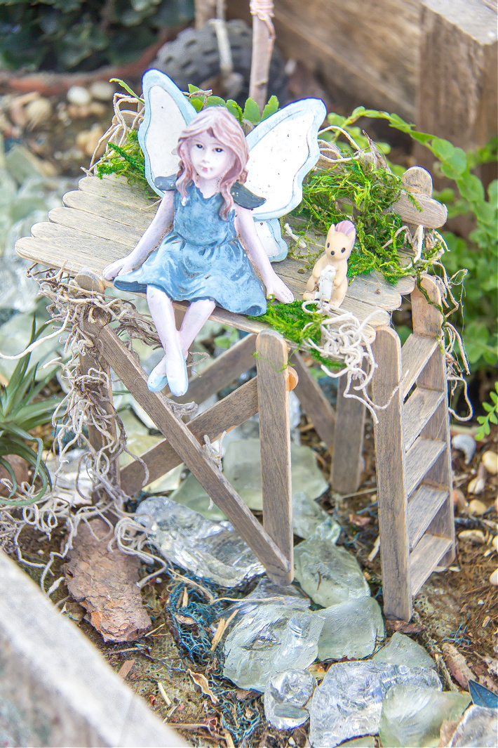 A fairy sitting on top of an observation deck made out of popsicle sticks inside a fairy garden.