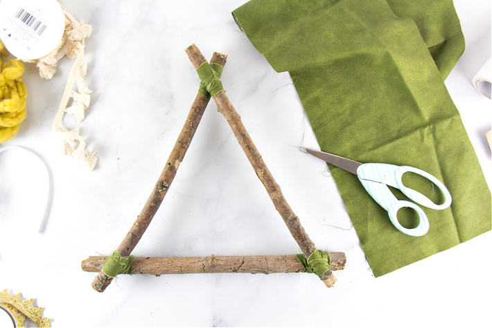 Sticks in a triangle shape tied together with strips of fabric.