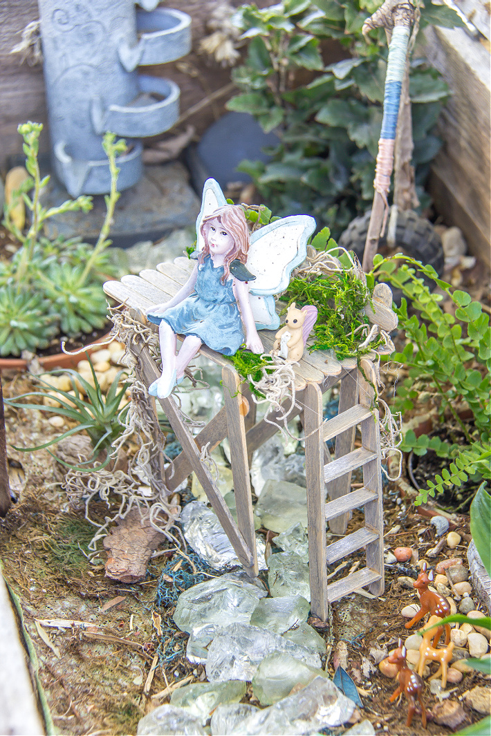 A fairy garden with a handmade popsicle stick observation deck and a fairy sitting on it with a squirrel.