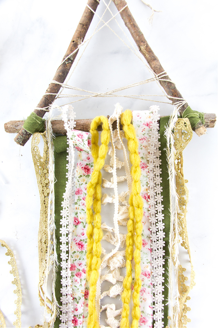 Ribbon, yarn, and scrap fabric being tied onto sticks.
