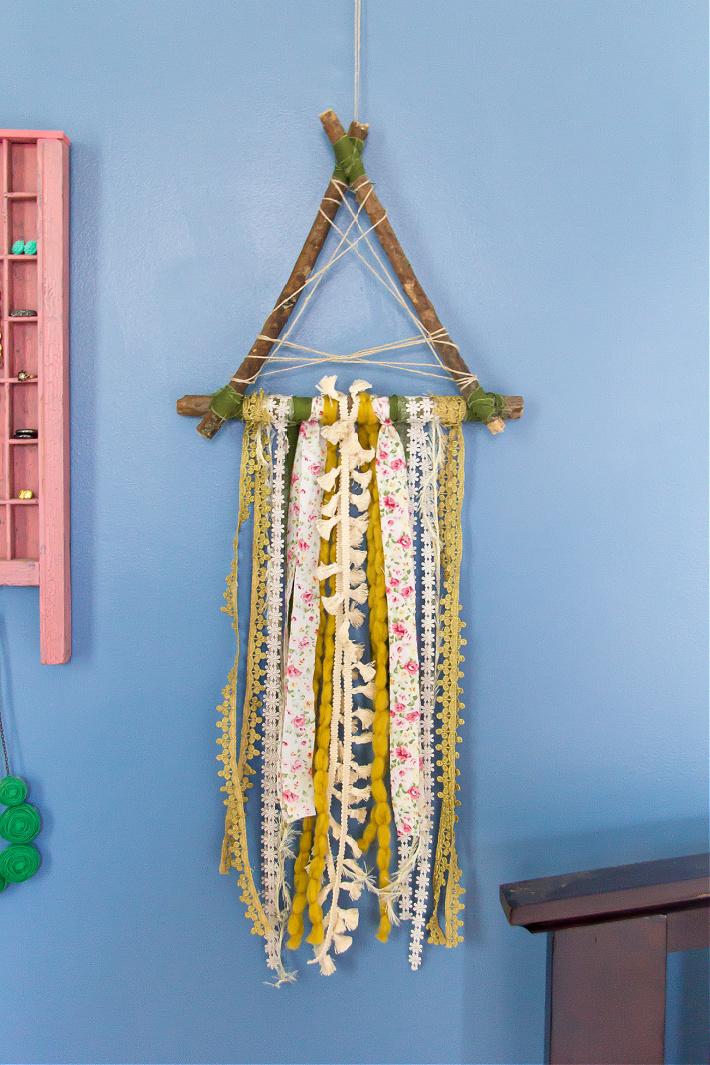 A handmade wall hanging using sticks and scrap materials.