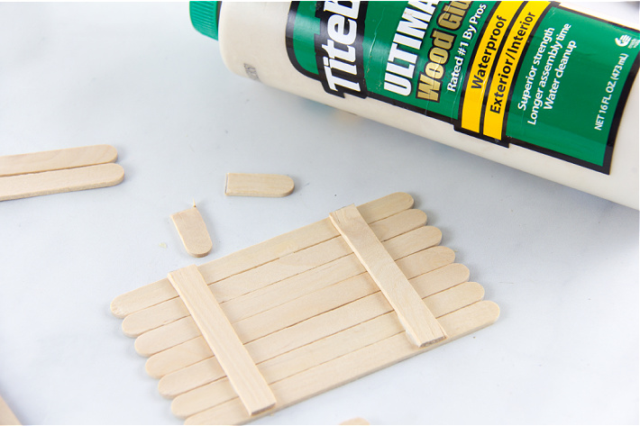 popsicle sticks lined up and being glued together
