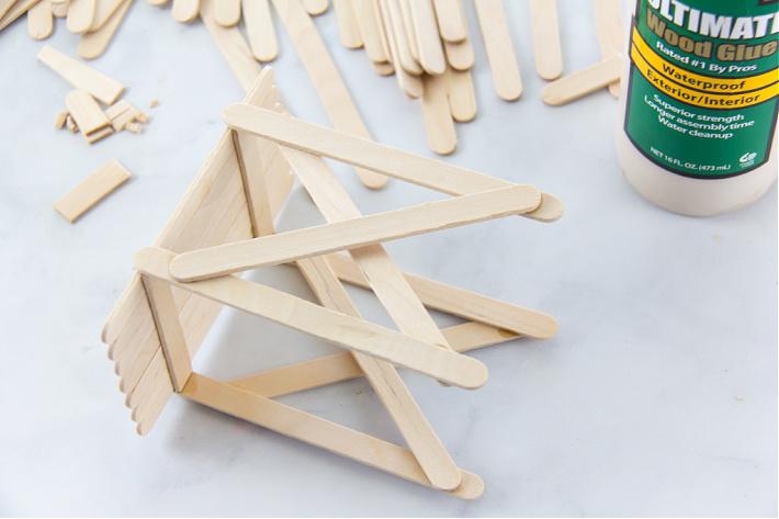 popsicle sticks being glued together to make an observation deck