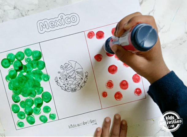 Toddler holding dot maker and making dots to complete mexican flag activity