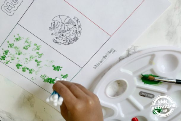 a toddler using ear buds to make dots to fill the mexican flag in corresponding colors