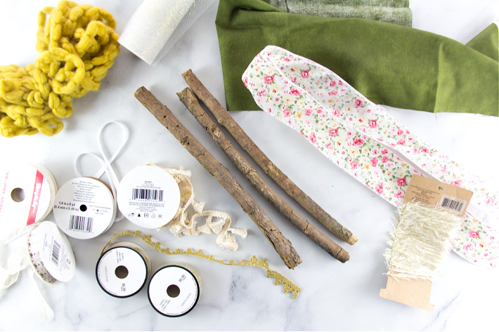 ribbon, sticks, and fabric to make a wall hanging