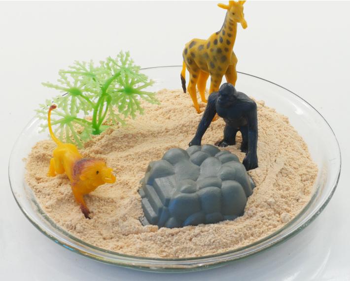 Sable comestible fini avec des jouets de sable dans un plat de cuisson profond prêt à jouer