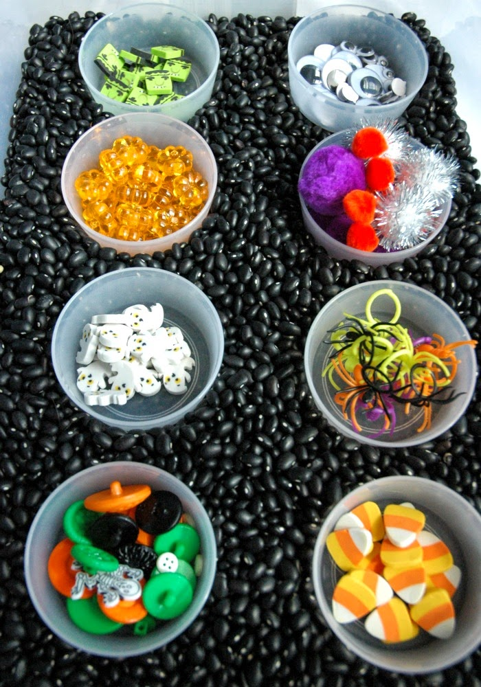 Halloween sensory bin idea with different Halloween themed items and black beans from Paper and Glue.
