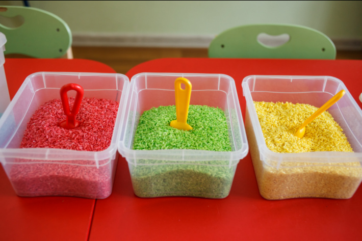 3 small sensory bins in plastic containers that are dry colored rice in red green and yellow