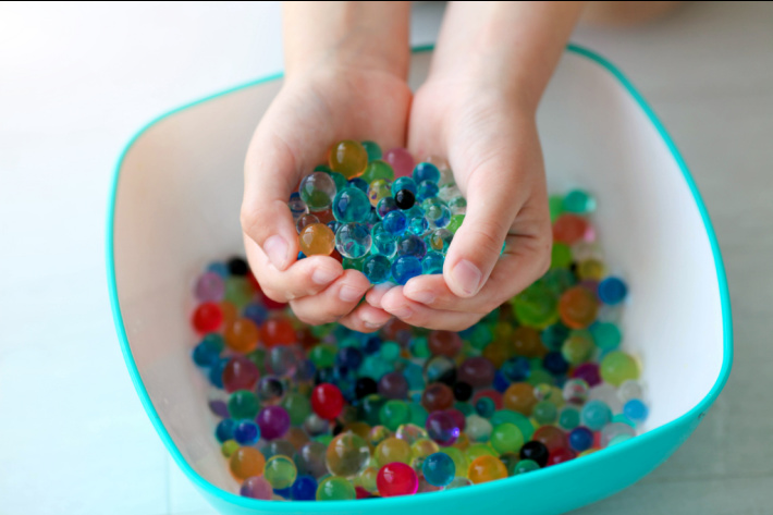 Water bead sensory play - Kids Activities Blog - child with water beads in hands over large plastic bowl