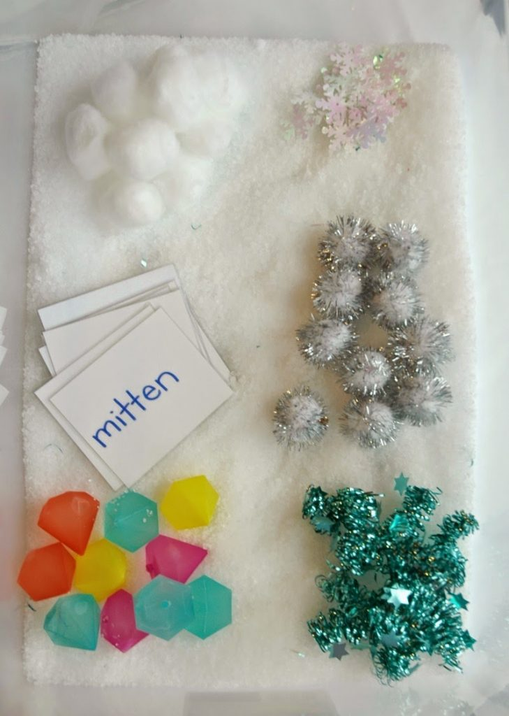 winter sensory bin from Paper and Glue has cotton balls snowflakes and other wintery items