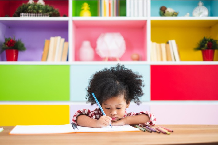 10 Awesome Free Handwriting Worksheets For Kids - Kid sitting at the table practicing handwriting on a worksheet in front of a colorful bookshelf