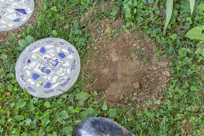 A shallow round hole dug in the ground to put a concrete stepping stone inside.