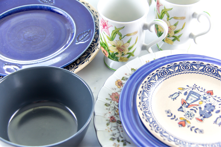 Mismatched plates, bowls, and cups for a mosaic concrete stepping stone DIY project for the garden.