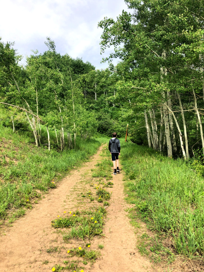 Hiking in Vail Colorado as a Family - Kids Activities Blog - Teenagers hiking down a deserted dirt road through aspen trees