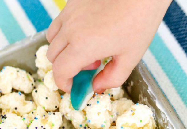La mezcla de senderos de cebo para tiburones tiene palomitas de maíz y otras cosas junto con tiburones de goma con la mano del niño
