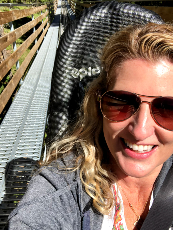 Ride the Forest Flyer roller coaster on the summit of Vail Mountain - Kids Activities Blog - Woman sitting in the Forest Flyer car with a selfie looking back on roller coaster track