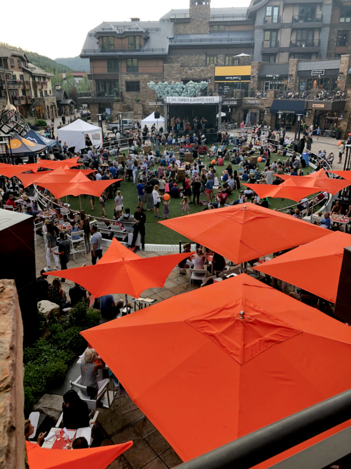 Vail Village Center Area - Solaris - Blue Grass Festival Tents - Kids Activities Blog - lots of orange tents and people gathered around the Blue Grass Festival concert