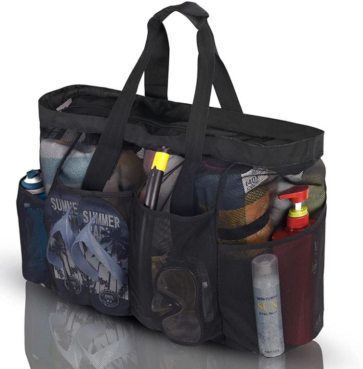 Bolsa de piscina de malla negra con cremallera en la parte superior y múltiples bolsillos laterales llenos de toallas, chanclas, snorkel, protector solar y más.