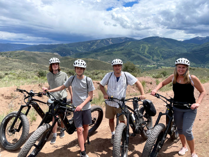 eBiking on unpaved mountain roads near Vail Colorado - Kids Activities Blog - Family of 4 with eBikes on the mountains looking back at the Vail Valley