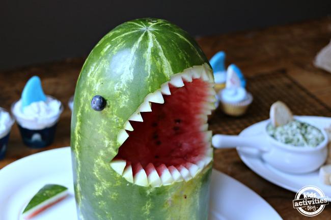 Sandía cortada como un tiburón con afilados dientes de tiburón y ojo de arándano