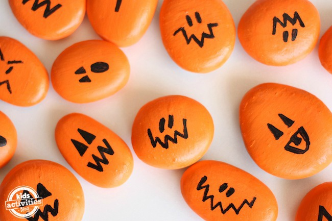 Painted pumpkin halloween rocks with orange stones and jack o lantern faces