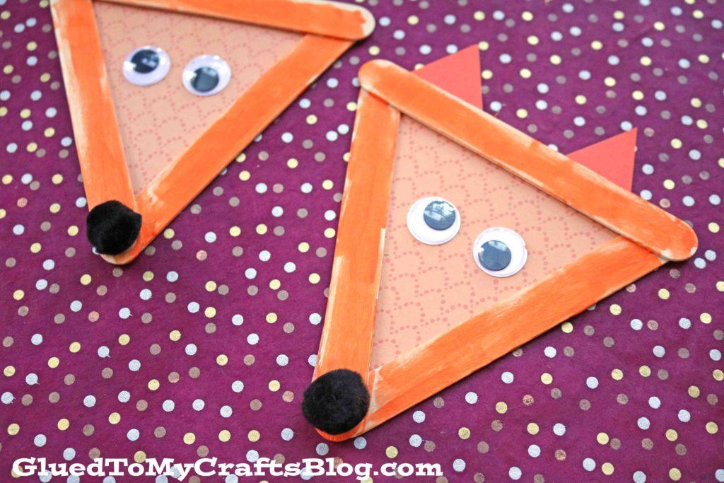 artisanat de renard en bâton de popsicle pour les enfants de Glued to My Crafts Blog - deux renards en bâton de popsicle finis montrés avec des yeux écarquillés