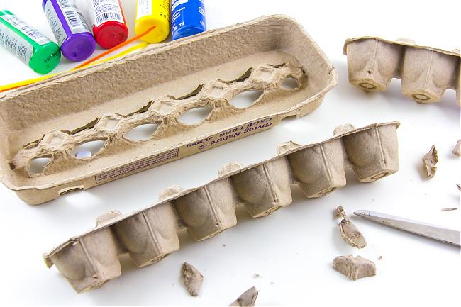 A brown egg carton being cut in half to make egg carton caterpillars