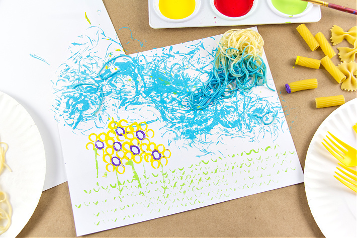 Rigatoni and spaghetti dipped in paint to make a painting of grass, sky, and flowers.
