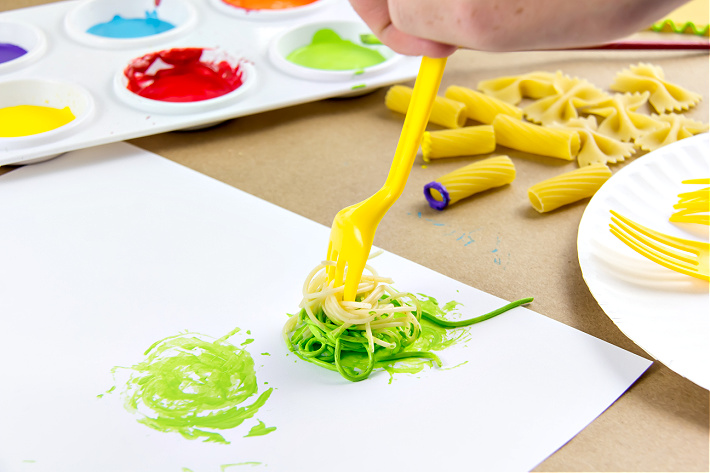 Spaghetti dipped in green paint and twirled around a plastic fork to make spaghetti art.