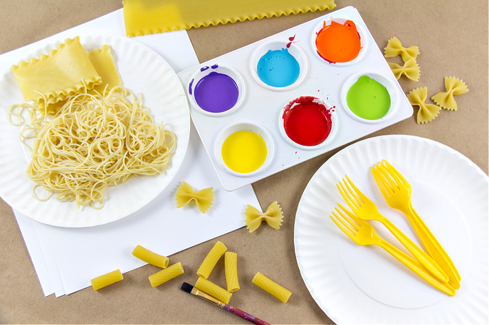 Supplies to make pasta art with kids including paper plates, paint, paper, and pasta.